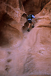Hiker climbing slickrock cliff, Coyote Gulch, Grand Staircase-Escalante National Monument, Utah