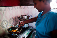 Razia Shabnam (in blue) cooks lunch for her son at home in Ekbalpore, Calcutta, West Bengal, India. Razia Shabnam, 28, was one of the first women boxers in Kolkata. She was also the first woman in her community to go to college. She is now a coach and one of only three international female boxing referees in India.  Photo by Suzanne Lee for Panos London