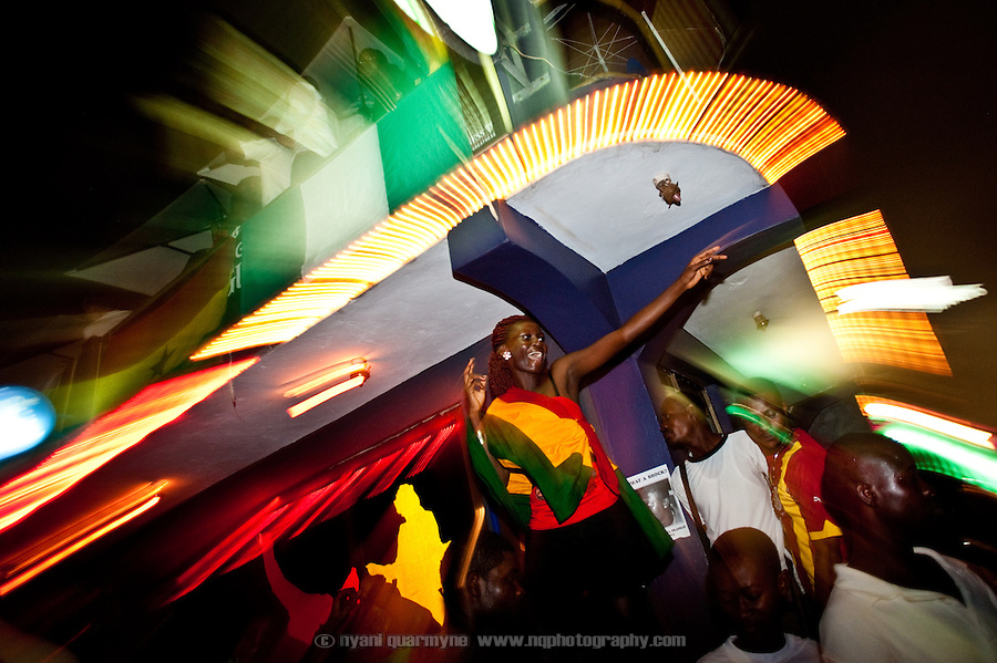 A woman dances on a table at Epo's, a popular nightspot in Accra, Ghana, after watching Ghana defeat the USA on 26 June 2010 during the FIFA World Cup.