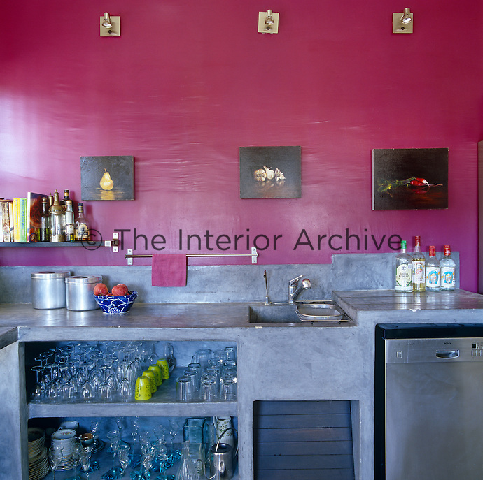 In this bright contemporary kitchen the open shelving is constructed from concrete and the walls are painted a vivid fuschia pink