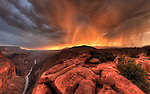 An ancient volcanic cinder cone comes back to life on the edge of the Grand Canyon with a little help from the setting sun and a monsoon curtain of rain.