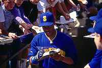 TEMPE, AZ - Ken Griffey Jr. of the Seattle Mariners signs autographs before a spring training game at Tempe Diablo Stadium in Tempe, Arizona in 1991. (Photo by Brad Mangin)