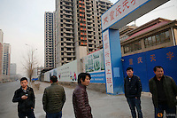 Migrant workers stand in front of the construction site of Zixia Garden development complex in Qianan, Tangshan City, Hebei province, China January 28, 2016.   REUTERS/Damir Sagolj