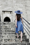 Elegant woman in blue dress on a starcase entering a medieval castle. Cyprus, Kolossi castle.