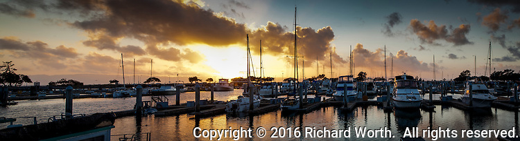 In this panoramic image, the setting winter sun finds its way through billowing clouds and casts golden light on sail boats moored at the San Leandro Marina