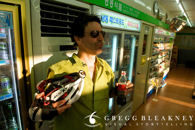 Greg McCormack cools off w/ Juffy Mart AC after long day cycling in the heat- Jeju Island - South Korea