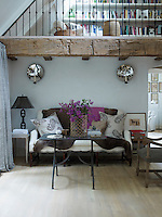 A renovated beam from a 1936 cottage supports the mezzanine floor above the living area