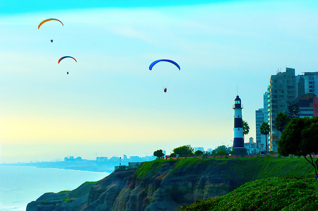 Paragliders soar over the Pacific cliffs on the Costa Verde in the district of Miraflores in Lima, Peru.  The El Faro Lighthouse is a famous landmark in the area.