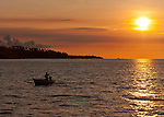 A fisherman in a small outrigger makes his way back to port at sunset.  Off Wori, North Sulawesi, Indonesia.