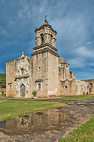 Another verticle view of the historic Mission San José y San Miguel de Aguayo a Catholic mission in San Antonio, Texas, United States. Just after the rain finished it left this pool of water that captures the reflection of the mission.  The dark sky were still threating more but lucky for us it never rained again. This one of the many mission built back in the 1700s that have been well preserved and or still functioning as a church today. This historic landmark was a spanish mission community which was design to convert the indians of the area to the catholic religion. These missions are now part of the world heritage site, along with the San Antonio Missions National historic Park. These mission are visited by many tourist and they have become a travel destination for many who visit San Antonio.Watermark will not appear on image