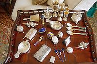 A mahogany tray table in the drawing room displays a collection of silverware