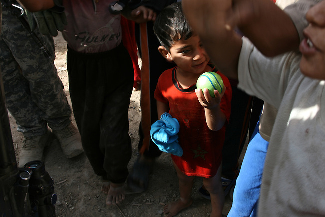 A boy appears pleased with a ball that has been given to him by a U.S. soldier in the village of Gazeelja, in Diyala province, Iraq. June 7, 2007. DREW BROWN/STARS AND STRIPES