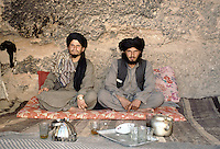 Two Taleban leaders having green tea and sweetie at the foot of the 54 meters Bamiyan Buddha in 1999. The destruction of the statues and fresco have already started.