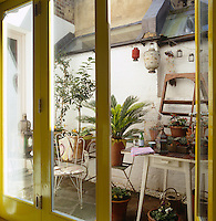 French windows painted yellow lead out onto a small paved courtyard filled with potted plants