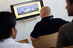 BAA staff watching security awareness film while awaiting issue of security passes at Heathrow airport.