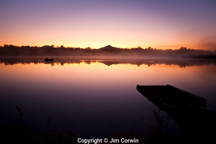 Sunrise in fog Lake Cassidy with dock along shoreline with Mount Pilchuck and fisherman in small boat