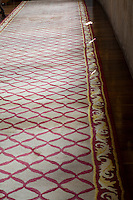 A detail of a red patterned carpet in a corridor in Parador hotel, Hostal dos Reis Catolicos