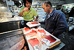 A buyer inspects slithers of tuna fish at Tsukiji fish market in Tokyo on Oct. 31, 2008. .Photographer: Robert Gilhooly