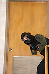 A woman police officer in training holding a paint ball simulated gun clearing a stairwell in a school shooting scenario