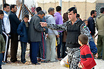 A Jordanian police officer directs a boy as he works to establish order during a public distribution of bread in the Zaatari Refugee Camp, located near Mafraq, Jordan. Opened in July, 2012, the camp holds upwards of 50,000 refugees from the civil war inside Syria, but its numbers are growing, and tensions inside the camp regularly boil over into incidents where the police have had to intervene. International Orthodox Christian Charities and other members of the ACT Alliance are active in the camp providing essential items and services.