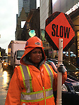 NYC, NY, USA. 19th Nov. 2015. Construction worker, wearing bright orange reflective rain gear, is holding SLOW sign by street construction in Times Square, Manhattan, the day after an ISIS propaganda video threatening New York City came out. NYC's Mayor and Police Commissioner both said there is no specific and credible threat against New York City.