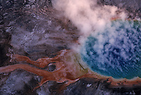Aerials of Grand Prismatic Geyser.  Yellowstone is the nations first National Park, it spans three states and holds 70% of the world's geothermal activity.<br /> The vivid colors in the spring are the result of pigmented bacteria in the microbial mats that grow around the edges of the mineral-rich water. The bacteria produce colors ranging from green to red; the amount of color in the microbial mats depends on the ratio of chlorophyll to carotenoids. In the summer, the mats tend to be orange and red, whereas in the winter the mats are usually dark green.[5] The center of the pool is sterile due to extreme heat.<br /> The deep blue color of the water in the center of the pool results from a light-absorbing overtone of the hydroxy stretch of water.[6] Though this effect is responsible for making all large bodies of water blue, it is particularly intense in Grand Prismatic Spring because of the high purity and depth of the water in the middle of the spring.