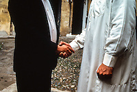 Torino,  due persone in abito bianco e nero si stringono la mano; stretta di mano interreligiosa Turin, two people in black and white dress shake hands; close interfaith hand