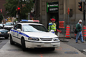 Montreal police car and officer block access to downtown street for crowd control at an event