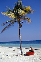 Man sitting in a beached dinghy under a loneplam tree, Puerto Morelos, Quintana Roo, Mexico