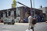 """Murals grace the walls in the so-called """"Five Points of Bushwick"""" in the Bushwick neighborhood of Brooklyn in New York on Saturday, April 27, 2013.  The owners of the buildings has allowed graffiti and street artists to decorate the blank walls of the industrial buildings. The neighborhood is undergoing gentrification changing from a rough and tumble mix of Hispanic and industrial to a haven for hipsters, forcing many of the long-time residents out because of rising rents.  ©Frances M. Roberts)"""