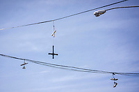 Sneakers and crosses hang from electrical lines in the Bushwick neighborhood of Brooklyn in New York on Saturday, April 19, 2014. The neighborhood is undergoing gentrification changing from a rough and tumble mix of Hispanic and industrial to a haven for hipsters, forcing many of the long-time residents out because of rising rents.. (©Richard B. Levine)
