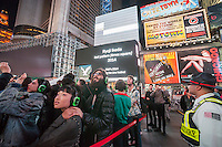 "Wearing wireless headsets, hundreds of visitors watch ""test pattern (times square)"" by the artist Ryoji Ikeda while listening to the artist's composed soundtrack just before midnight on Thursday, October 16, 2014. As part of the ""Midnight Moment"" the artist has taken over multiple screens in Times Square from 11:57 PM to midnight with his flickering images. A monthly event the Midnight Moment invites daily  three minute performances from artists every month. This is the first time sound has been incorporated into a viewing.  (© Richard B. Levine)"