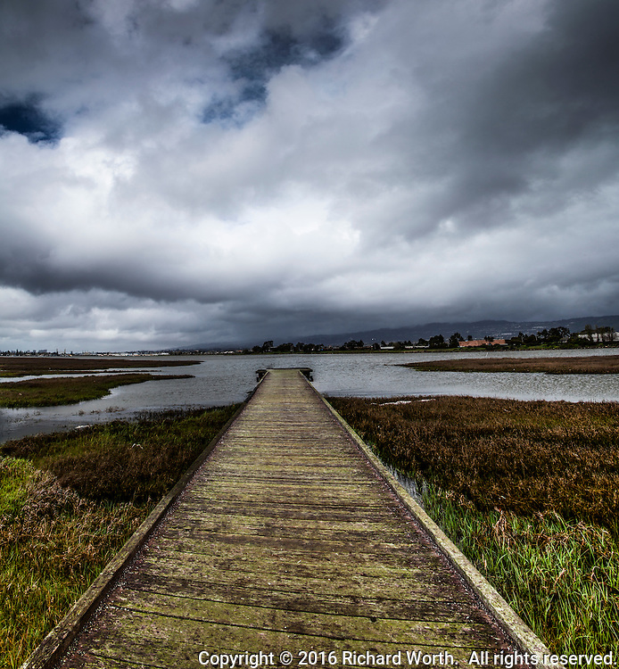 Clouds fill the sky and an observation platform stretches into San Leandro Bay at the Martin Luther King Jr. Regional Shoreline in Oakland, California.
