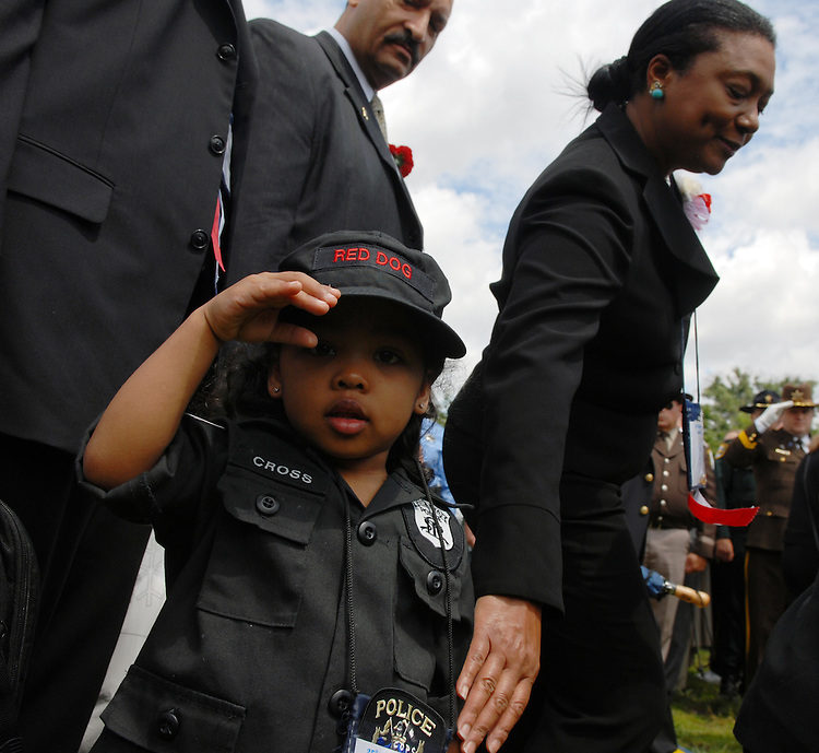 The daughter of Off. Mark Anthony Cross of the Atlanta PD, salutes the camera during the procession of family members of fallen officers at the 25th Annual National Peace Officers' Memorial Service.