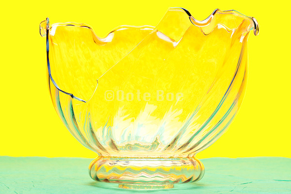 broken clear glass lampshade object on yellow green background