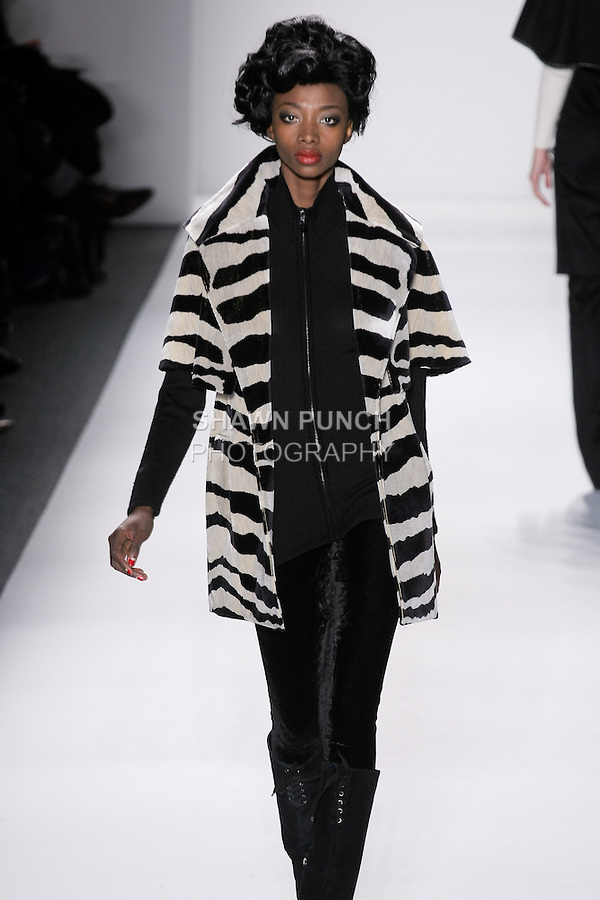 """Model walks runway in a black+ivory clarence house silk velvet zebra mini storm coat, black handloomed cashere/silk zipped ribbed turtleneck+velvet leggings, from the Zang Toi Fall 2012 """"Glamour At Gstaad"""" collection, during Mercedes-Benz Fashion Week New York Fall 2012 at Lincoln Center."""