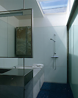 In this bathroom a suspended mirror above the stainless steel basin unit screens off the bath and houses a concealed light