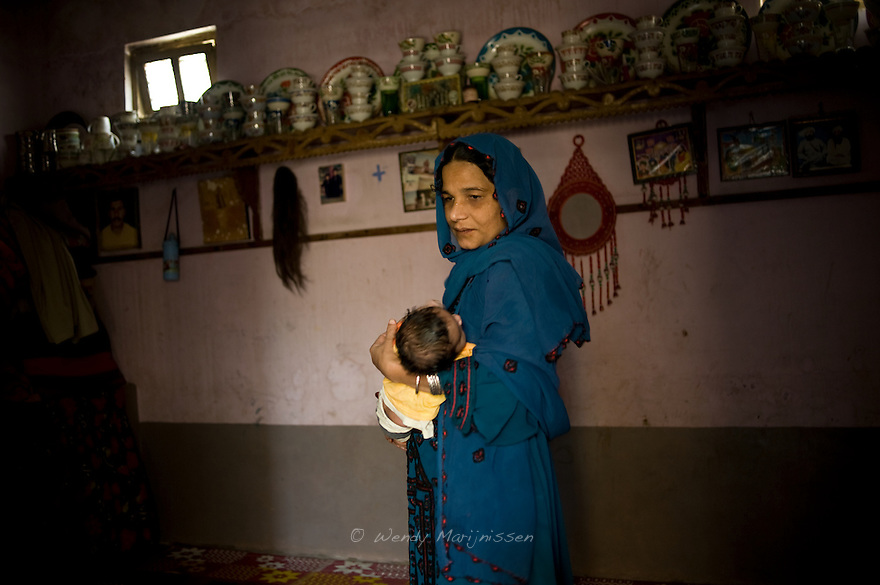 Ghair Bibi's daughter Kasbano holds her two-month-old baby boy. <br />