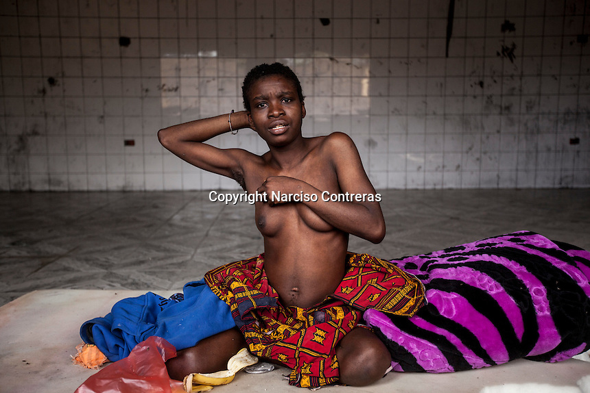 A mentally ill sub-Saharan illegal migrant strips inside an isolated cell in a Surman detention centre, revealing an abortion scar on her belly. A local doctor says that the woman, presumably a rape victim, has been detained for the last two years. When asked about the woman's scar he replies that it is unclear if she became pregnant whilst in custody, or beforehand.
