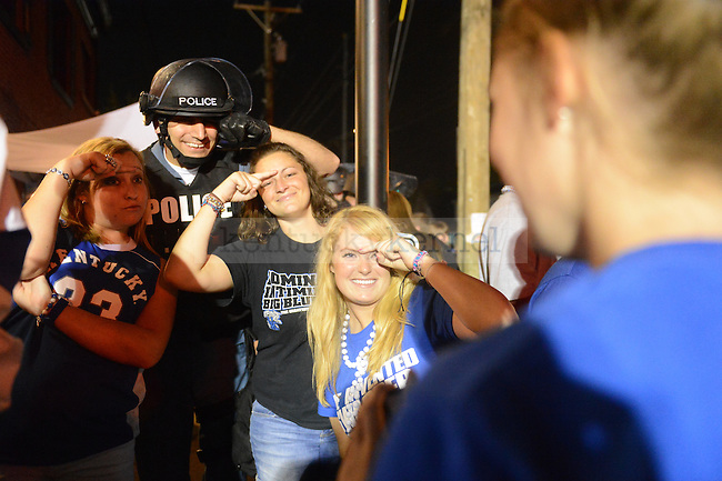 UK fans celebrate with a Lexington police officer at the intersection of Woodland Ave. and Euclid Ave. in Lexington, Ky., after their victory over Kansas in the NCAA Basketball Championship game on 4/3/12. Photo by Mike Weaver | Staff