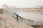 BAGHDAD, IRAQ: A rower on the Iraqi olympic rowing team bring their boat down to the Tigris in the morning...Despite dangers like kidnappings, bombs, and assassinations, Iraq's olympic rowing team prepares for the London 2012 Summer Olympics...Photo by Ali Arkady/Metrography