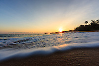 A rushing wave reflects the golden sunrise at Secret (or Secrets) Beach, North Kaua'i.