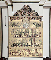 Calligraphy panel in the Grand Mosque or Ulu Cami, built 1396-99 under the Ottoman Sultan Bayezid I by the architect Ali Neccar in the Seljuk style, Bursa, Turkey. The mosque contains 192 monumental wall inscriptions written by the famous calligraphers of that period. The mosque is a large rectangular building with 2 minarets, and 20 domes supported by 12 columns. Supposedly the 20 domes were built instead of the 20 separate mosques which Sultan Bayezid I had promised for winning the Battle of Nicopolis in 1396. The dome over the sadirvan is capped by a skylight creating a soft light which illuminates the large building. The mosque is in the old city centre of Bursa and remains the largest mosque in the city. Picture by Manuel Cohen