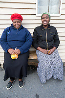 South Africa, Cape Town, Guguletu Township.  Two Women Sitting on a Bench.