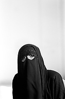 Iraq. Baghdad. Iraqi women league. A widow wears the niqab and the abaya.  She has lost her husband in january 2004 who got sick from the years spent in jail and tortured by the Saddam Hussein regime. The abaya, sometimes also called aba, is a simple, loose over-garment, essentially a robe-like dress, worn by some women in parts of the Islamic world. Traditional abaya are black and may be either a large square of fabric draped from the shoulders or head or a long caftan. The abaya covers the whole body except the face, feet, and hands. It can be worn with the niqab, a face veil covering all but the eyes. Some women choose to wear long black gloves, so their hands are covered as well. A niqab is a cloth which covers the face, worn by some Muslim women as a part of sartorial hijab. 20.02.04 © 2004 Didier Ruef