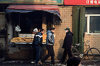 People walk past a small bakery in Urumqi, Xinjiang, China.