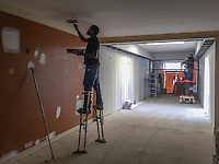 Worker uses stilts to apply sparkle to sheetrock installed at a restaurant in Uptown Westerville