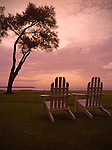 Adirondack chairs sit on a grassy field at sunset.