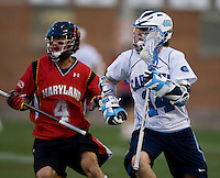 Gavin Petracca (14) looks for a teammate while being defended by Dan Burns (4) of Maryland during the ACC men's lacrosse tournament semifinals in College Park, MD.  Maryland defeated North Carolina, 13-5.