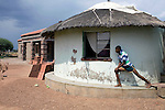 GA-MASEHLONG, SOUTH AFRICA -  MARCH 28: An unidentified brother of Caster Semenya stretches outside the family house on March 28, 2010, in Ga-Masehlong, South Africa. Caster Semenya, age 19, a runner who won the 800 meters world cup title in Berlin, Germany in 2009. She was later gender tested as she blew away the competition. She has not competed in any race since then but she is still a role model for relatives and children in the rural poor village. She was raised in the on the right and the newly constructed house is a gift from the local government. (Photo by Per-Anders Pettersson/Getty Images